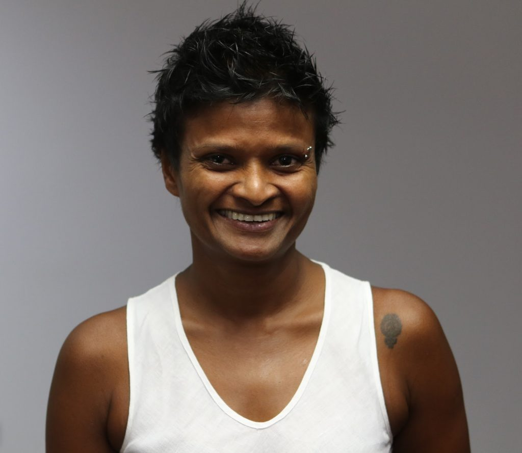 Photo of Jayanthi Kuru-Utumpala in a white shirt smiling at the camera