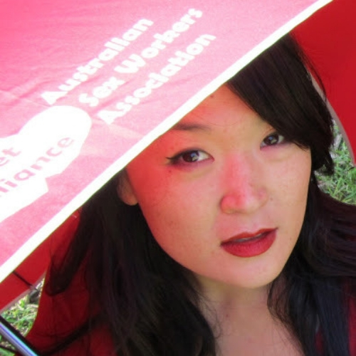 photo of jules kim looking up at the camera from under a red umbrella wearing red lipstick