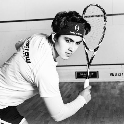 black and white photo of Maria Toorpakai Wazir posing with squash racket while looking off camera, wearing a headband