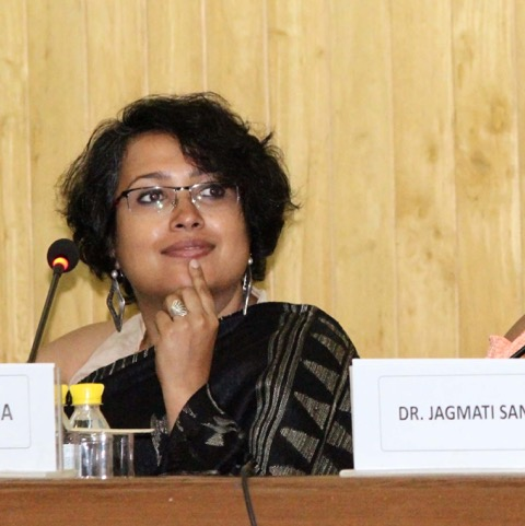 Photo of Payoshni Mitra showing head and shoulders whiles she is sitting on a panel and holding her hand to her chin