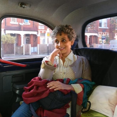 Photo of Arundhati Roy sitting in the backseat of a car with her chin resting on her hand