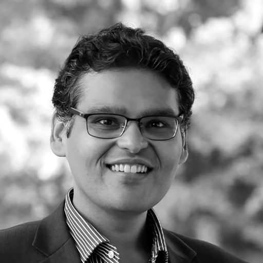 black and white photo of nishant shah smiling at camera showing shoulders and head