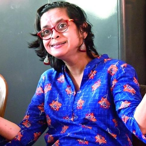 Photo of Jeeja Ghosh wearing a blue shirt and red glasses