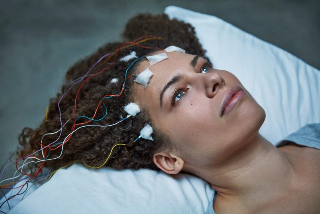 woman's head on pillow with transmitters attached to forehead
