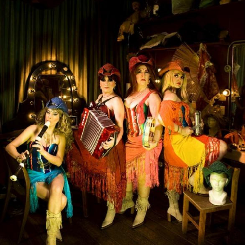four performers in colorful dresses holding musical instruments